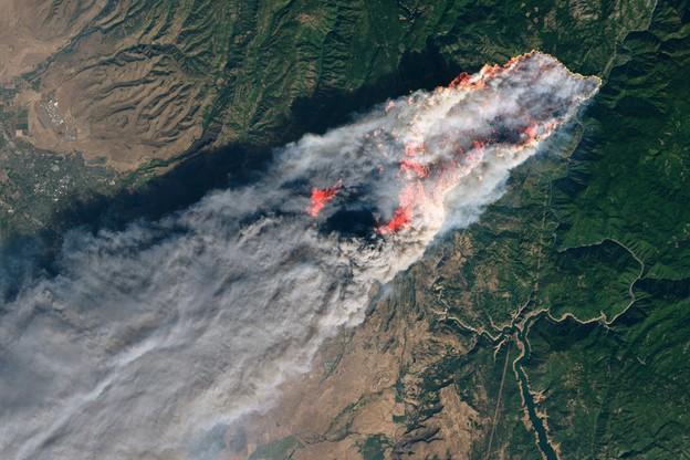 Zdjęcie Kalifornii wykonane z orbity - znaczny obszar zajęty przez ogień i zasnuty dymem.