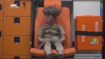 Zakrwawiony, pokryty kurzem chłopiec wyciągnięty z gruzów. Przeżył bombardowanie w Aleppo
