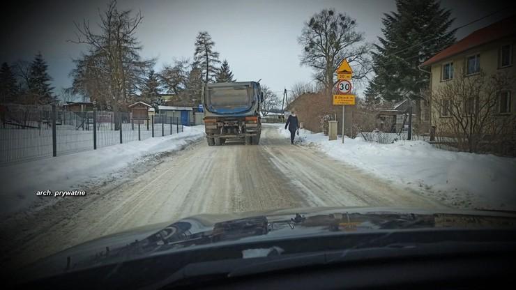 Sznur ciężarówek przejeżdża przez wieś. Nie ma chodnika ani pobocza