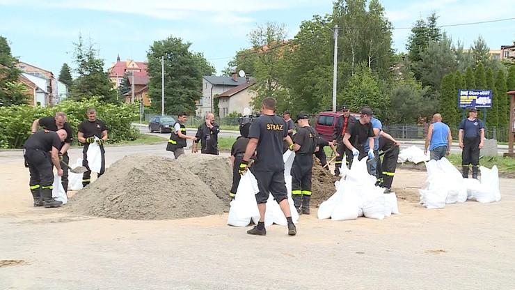 Strażacy napełniają worki piaskiem