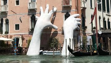 Ręce wynurzające się z wody w Wenecji. Mają zwrócić uwagę na globalne ocieplenie
