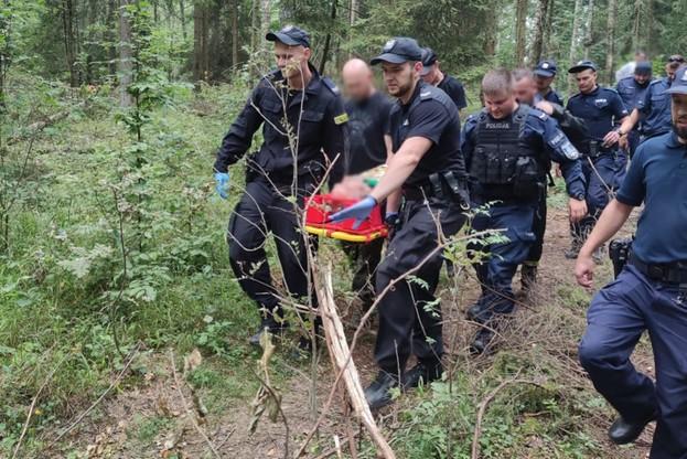 Policjanci niosący odnalezionego mężczyznę