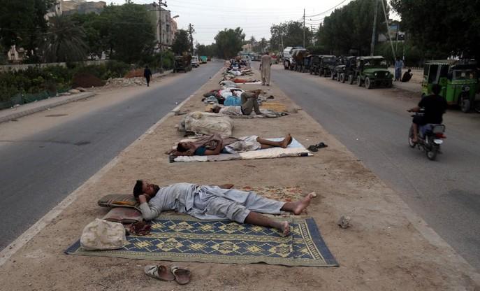 Bezdomni śpią na ulicy w Pakistanie, po tym, jak władze wprowadziły tzw.