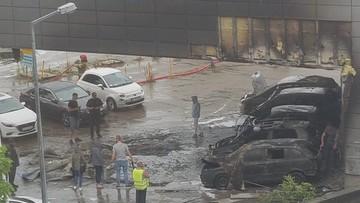 Kłęby dymu nad miastem i spalone samochody
