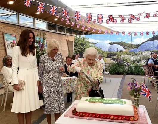 Królowa Elżbieta druga kroi tort mieczem