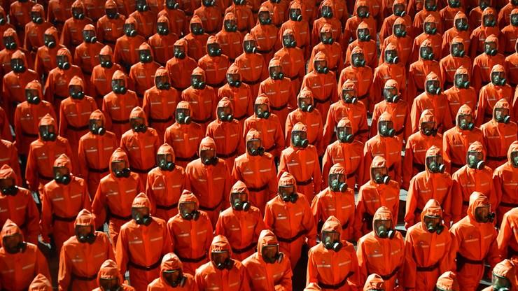 Defilada w Korei Północnej. Szeregi żołnierzy w kombinezonach ochrony biologicznej