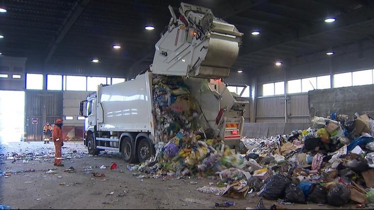 Rząd kolorowych pojemników do recyklingu i jedna śmieciarka. Mieszkańcy są oburzeni